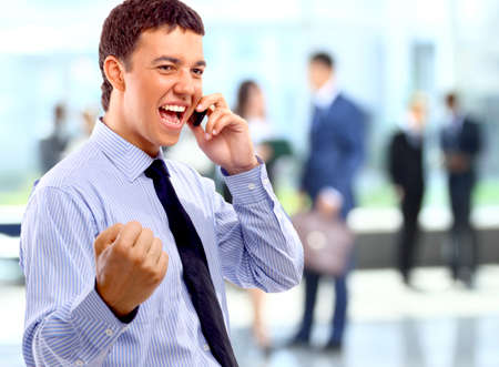 Portrait of happy businessman talking on mobile in office lounge  photo