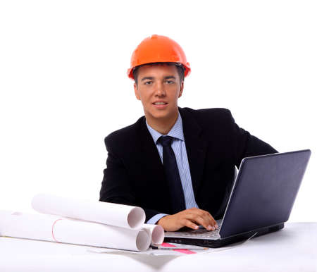 Construction contractor in the office on his laptop  Isolated on white  photo