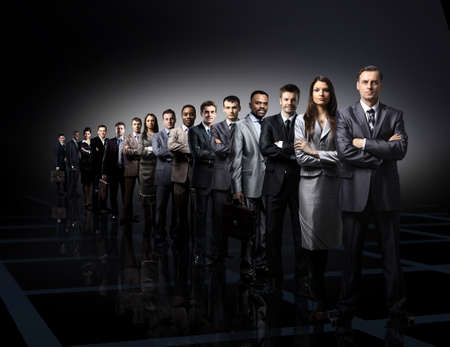 ビジネス チームは、暗い背景の上に立っている若いビジネスマンの形成 写真素材