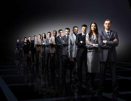 business team gevormd van jonge ondernemers permanent over een donkere achtergrond