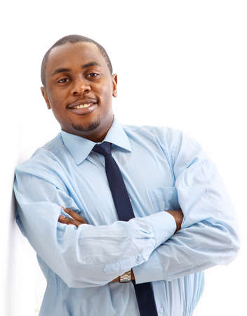 Portrait of a happy young African American business man with hands folded on white  photo