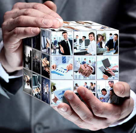 technology collage: cube with business collage in the businessman hands Stock Photo
