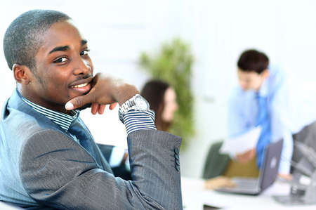 black business men: Portrait of smiling African American business man with executives working in background Stock Photo