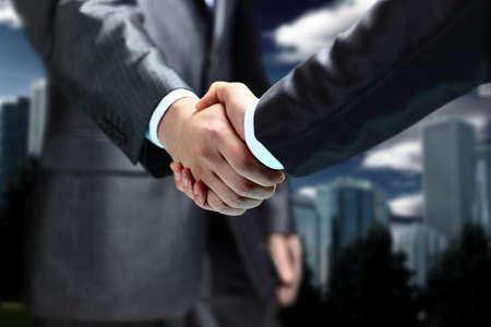Handshake - Hand h?lt auf schwarzem Hintergrund Standard-Bild
