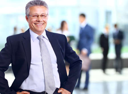 mature male: Successful business man standing with his staff in background at office Stock Photo