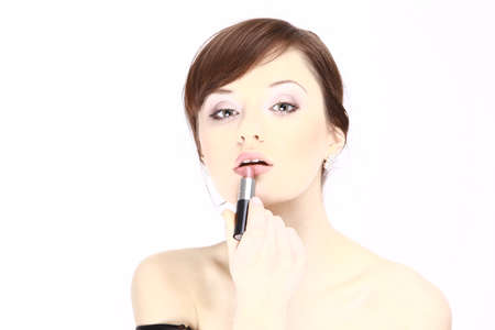 concealer: Portrait of beautiful woman applying lipstick using lip concealer brush