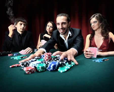 playing with money: Poker player going all in pushing his chips forward Stock Photo