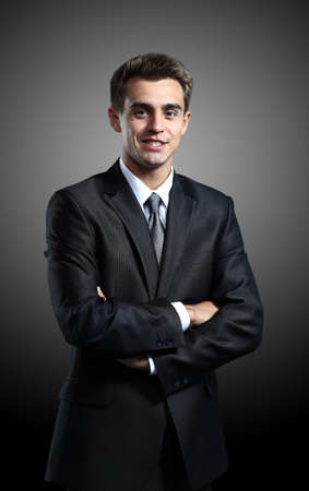 Portrait of successful business man standing on black background photo