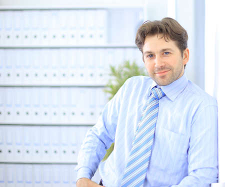 business lounge: Young businessman standing in office lobby, using smartphone, smiling Stock Photo