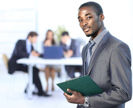 african business man: Portrait of a successful american african businessman smiling leading his team Stock Photo