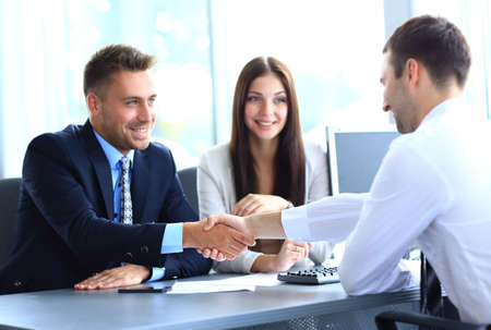 strong partnership:  businessman shaking hands to seal a deal with his partner