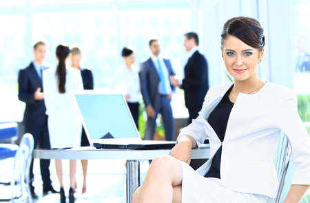 Portrait of a cute business woman smiling with people at the back Stock Photo