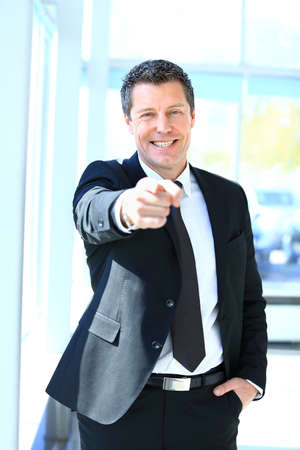 Portrait of smiling mature business man pointing at you in office photo