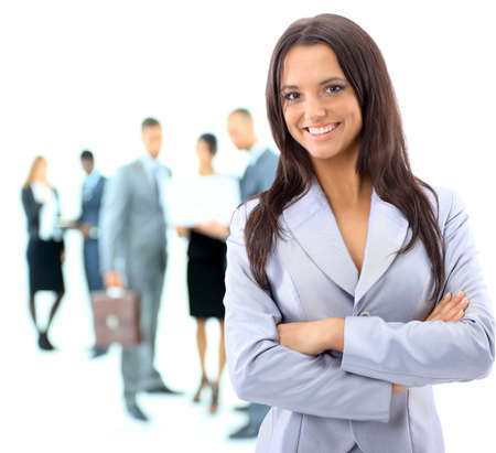business woman standing: Portrrait of a young business woman with people discussing in background Stock Photo