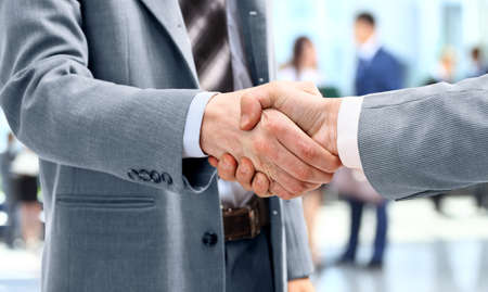 business men: Handshake in front of business people Stock Photo