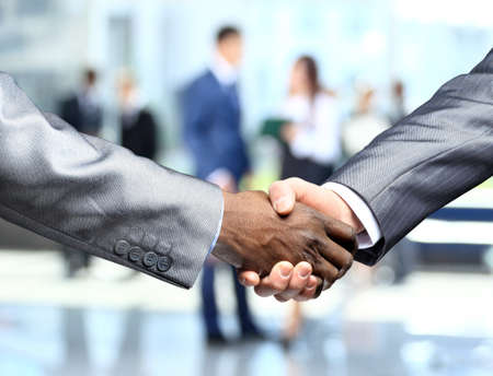 business handshake: Handshake in front of business people Stock Photo