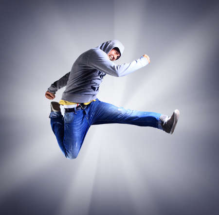 Portrait of an young man jumping in air against light background photo