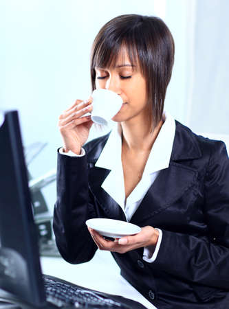 Businesswoman sitting at the table in office lobby, drinking coffee.  Stock Photo - 22476416