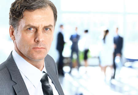 senior business: Business man at the office with a group behind him Stock Photo
