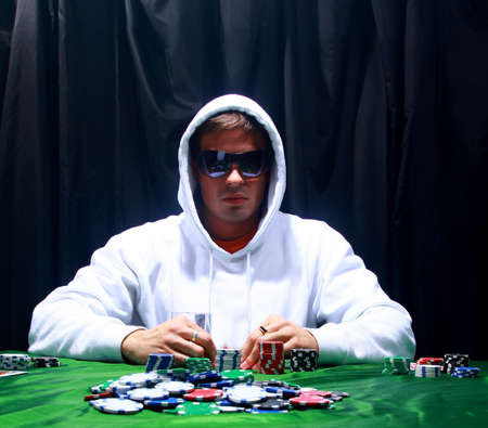 a poker player sitting at a table trying to hide his expressions  photo