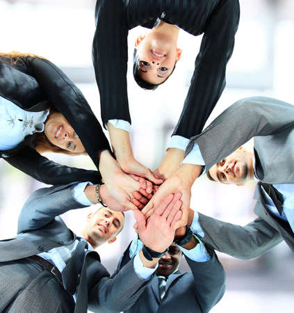 Small group of business people joining hands, low angle view. photo