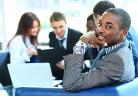 Portrait of smiling African American business man with executives working Stock Photo