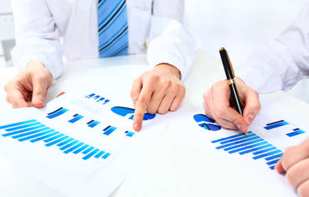 financial issues: Two business people discuss financial issues sitting at the business table with documents Stock Photo