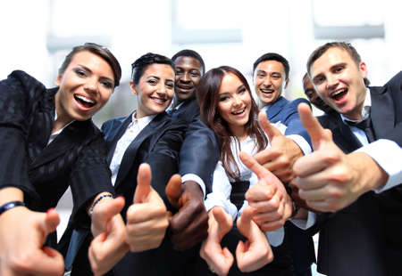 team victory: Successful business people with thumbs up and smiling Stock Photo