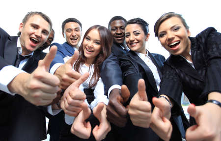 team victory: Happy multi-ethnic business team with thumbs up in the office