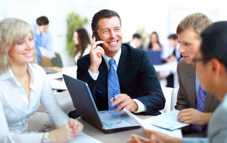 reuniones empresariales: Hombre de negocios hablando por tel�fono mientras en una reuni�n