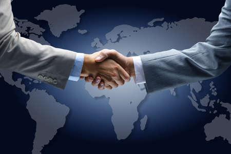 Poignée de main avec la carte du monde en arrière-plan