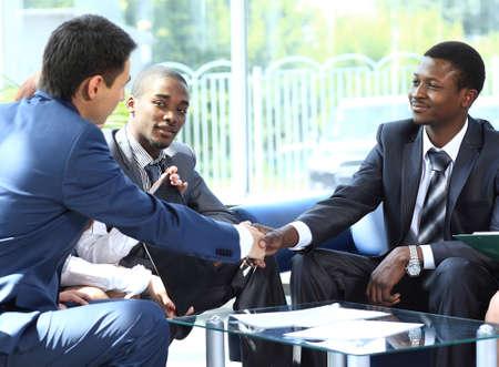 Deux homme d'affaires se serrant la main avec son équipe dans le bureau