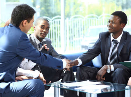 black men: Two business man shaking hands with his team in office Stock Photo