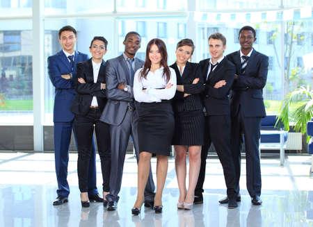 Glückliche junge Business-Frau mit ihrem Team im Hintergrund