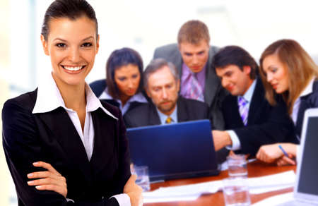 businessteamwork: Smiley businesswoman with a group behind him Stock Photo