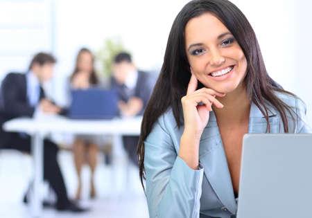 mujeres trabajando: Atractiva mujer de negocios sonriente joven usando la computadora portátil en el escritorio de trabajo