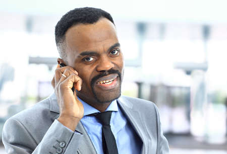 Attractive smiling Afro-American young businessman on phone in office photo