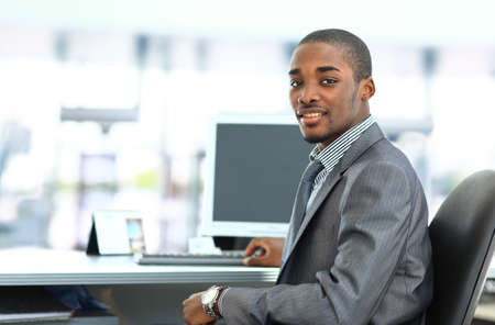 Portrait of a happy African American entrepreneur displaying computer laptop in office photo