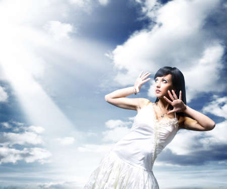 Happy young woman posing over blue sky photo
