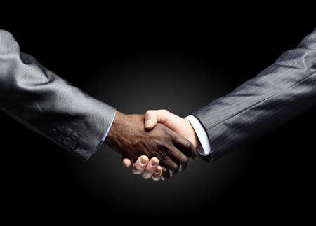 shake hand: African businessmans hand shaking white businessmans hand