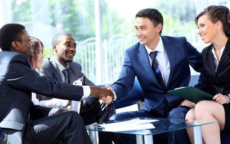 Dos hombre de negocios dándose la mano con su equipo en la oficina