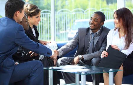 Zwei Geschäftsmann Händeschütteln mit seinem Team im Büro