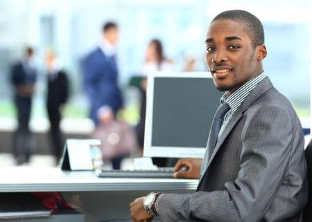 Portrait d'une afro-américains heureux entrepreneur affichage ordinateur portable dans le bureau