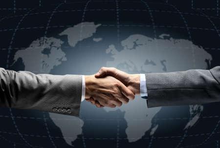 empleos: Apretón de manos con el mapa del mundo en el fondo