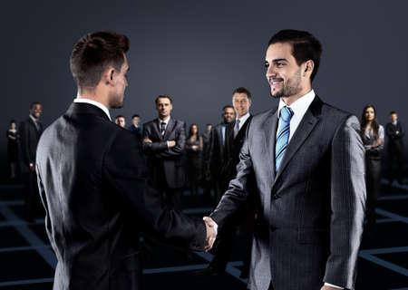 personas saludandose: Retrato de jóvenes empresarios. Apretón de manos delante de la gente de negocios