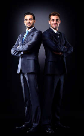 Two young businessmen full body, isolated on black photo