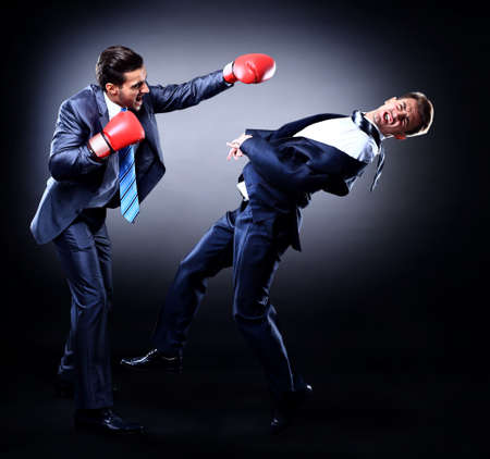 boxing sport: Two young businessman boxing againts dark background