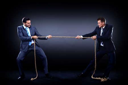 Due uomini d'affari che tirano la corda in una competizione, isolato su sfondo bianco