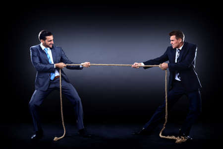 Two business men pulling rope in a competition, isolated on white background photo