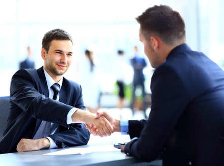 business smile: Dos colegas de negocios d�ndose la mano durante la reuni�n